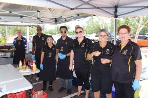 Staff volunteering to serve sausages to raise money